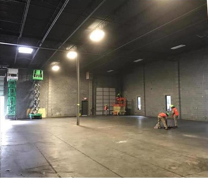 Warehouse or Storage area empty with a forklift and man cleaning