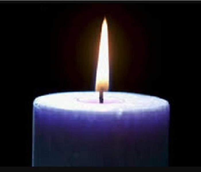 Purple candle with flame on black background