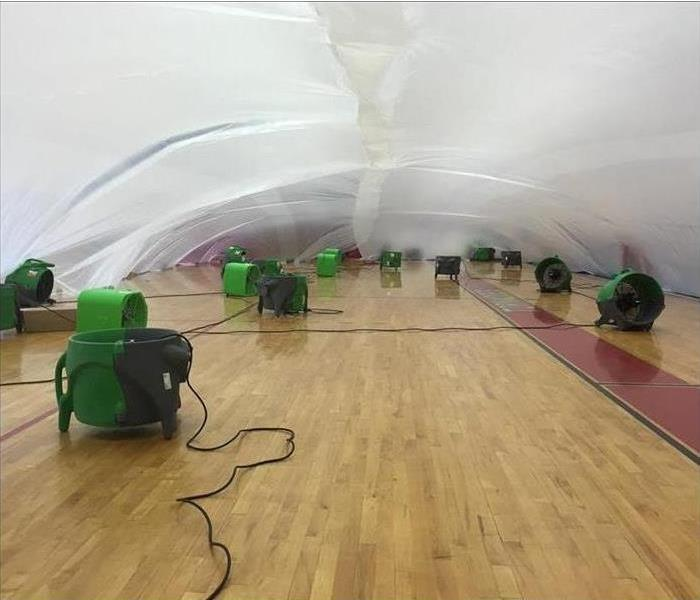 Plastic over a basketball gym floor with equipment under it.