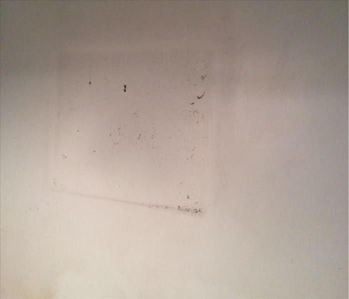 Wall with an outline of soot around where a picture hung from a fire damage.