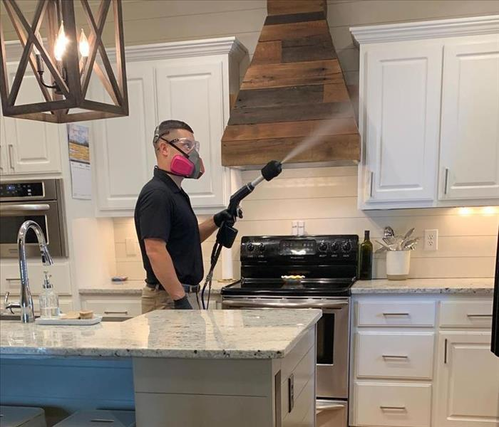 Man in full face respirator spraying disinfectant in a kitchen